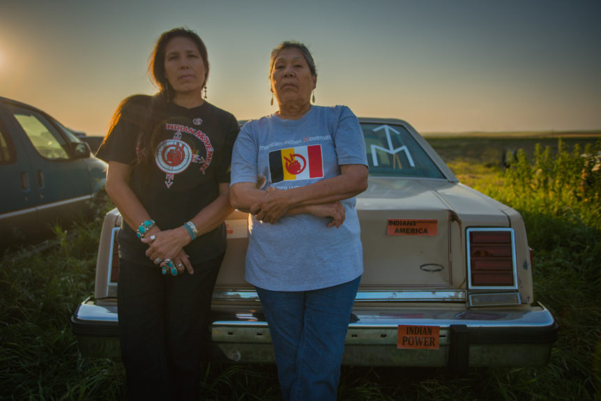 Two American Indian Women activist stand, cross-armed and empowered against a late model sedan with sticker(s) Indian Power on it